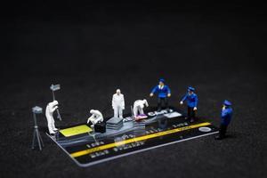 miniatuurpolitie en rechercheurs op een plaats delict op creditcards, cybercriminaliteitsconcept