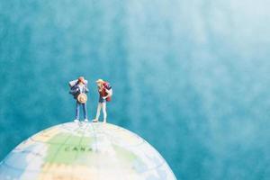 miniatuurreizigers met rugzakken die op een wereldbol staan en naar een bestemming lopen