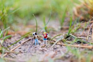 miniatuurreiziger met rugzakken die in het veld-, reis- en avontuurconcept lopen