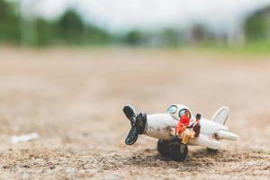 miniatuurpaar zittend op een vliegtuig, het wereldconcept verkennen foto