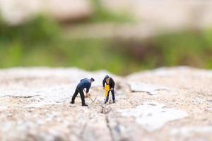miniatuurarbeiders die aan beton met scheuren, groepswerkconcept werken