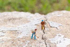 miniatuurarbeiders die aan beton met scheuren, groepswerkconcept werken foto