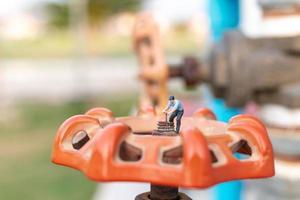 miniatuur loodgieter die waterleidingen installeert en schade aan een waterpompmachine controleert
