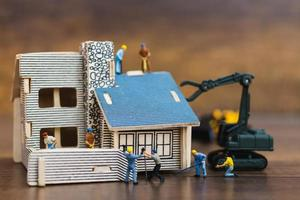 miniatuurarbeiders die een huis bouwen, het concept van de huisrenovatie