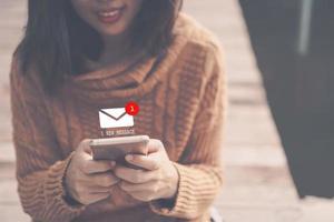 vrouw die smartphone gebruikt om e-mail te verzenden en te ontvangen