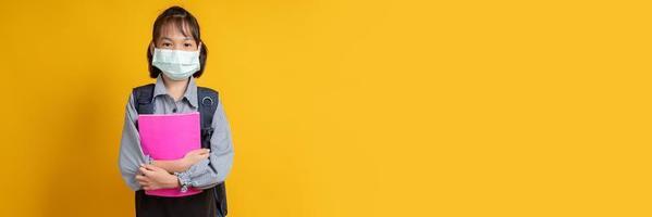 Aziatisch meisje dat gezichtsmasker draagt dat rugzak draagt en boeken houdt die camera met gele achtergrond bekijken foto