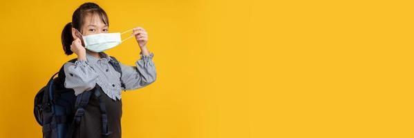 Aziatisch meisje dat gezichtsmasker draagt dat rugzak draagt die camera met gele achtergrond bekijkt foto