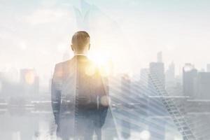 dubbele blootstelling van de achterkant van de man in pak kijken naar de skyline van de stad en zonlicht foto