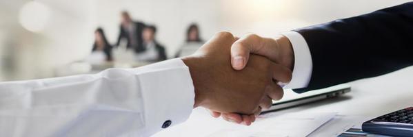 close-up van zakenlieden handen schudden met wazig mensen op de achtergrond foto