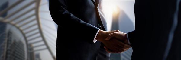 close up van zakenlieden handen schudden met wazig stadsgebouwen op de achtergrond foto