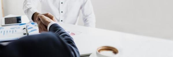 close-up van zakenlieden handen schudden op een wit bureau foto