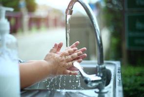 kind zijn handen wassen met zeep buitenshuis, hygiëne en schoonmaak concept foto