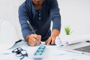 persoon die aan een blauwdruk werkt naast laptop en opgerold papier foto