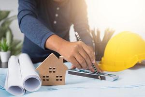 architect werkt aan een blauwdruk naast een helm, een pot met potloden en een huismodel foto