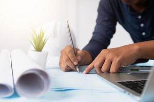 architect werkt aan een blauwdruk naast laptop en opgerold papier foto