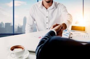close-up van zakenlieden handen schudden met de skyline van de wazig stad op de achtergrond foto