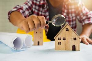 close-up van de mens met behulp van een vergrootglas op een huis-model met een harde hoed en opgerolde papieren foto