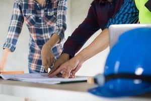 drie mensen wijzen een blauwdruk naast een bouwvakker foto