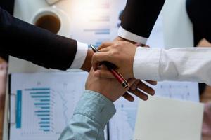close-up van vier handen op elkaar gestapeld over papieren van grafieken en grafieken
