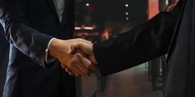 twee mensen schudden elkaar de hand met een wazige restaurantachtergrond foto
