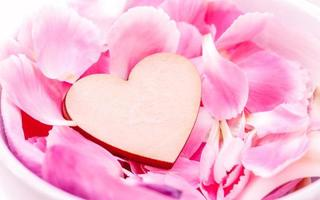 houten hart en roze bloemblaadjes foto
