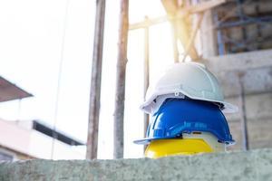 drie gestapelde witte, blauwe en gele harde hoeden op een bouwplaats foto