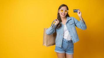 Aziatische vrouw met creditcard en papieren boodschappentas op gele achtergrond