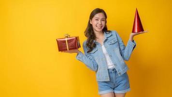 Aziatische vrouw met rode kegel feestmuts en rode geschenkdoos op gele achtergrond foto