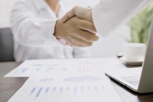 zakenmensen schudden elkaar de hand naast laptop met papieren van grafieken en diagrammen