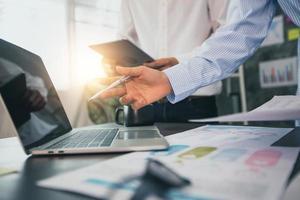 zakenlieden die op laptop en tablet werken naast papieren van grafieken en grafieken