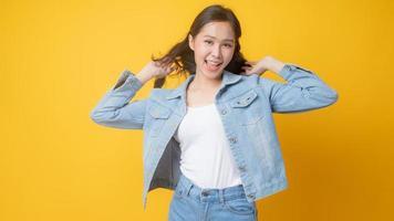 Aziatische vrouw glimlachend en spelen met haar haren op gele achtergrond foto