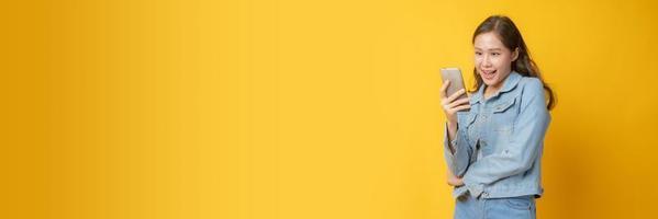 Aziatische vrouw glimlachend en kijken naar mobiele telefoon op gele achtergrond foto