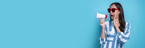 Aziatische vrouw met witte zonnebril en witte megafoon op blauwe achtergrond foto