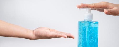 handen met blauwe ontsmettingsmiddelfles