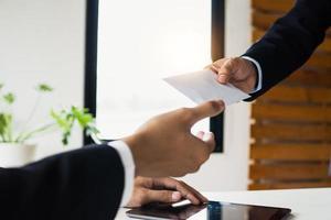 persoon die een leeg wit stuk papier overhandigt aan een andere persoon met een tablet in een kantoor foto