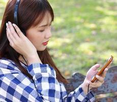 Aziatische vrouw ontspant gelukkig met muziek op smartphone in het park