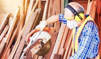 oudere Aziatische timmerman ambachtsman gebruikt cirkelzaag om hout voor meubels te verwerken foto