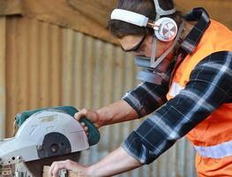 Aziatische timmerman-ambachtsman gebruikt cirkelzagen om hout voor meubels te verwerken foto
