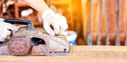 hand werken met met elektrische schaafmachine buitenshuis