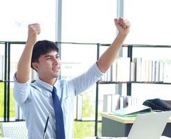jonge zakenman die gelukkig op kantoor werkt foto