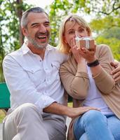 oudere blanke man verrast met geschenkdoos aan zijn mooie vriendin