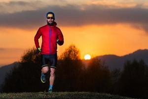 atletische man met baard racen in de bergen tijdens een kleurrijke zonsondergang van vuur foto