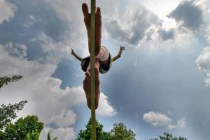 een jongeman op blote voeten die in evenwicht op een singel loopt