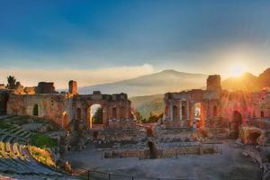 bijzonder van het oude theater van Taormina met uitbarstende vulkaan Etna bij zonsondergang