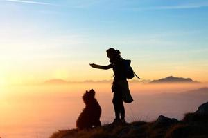 meisje speelt met haar hond in de bergen foto