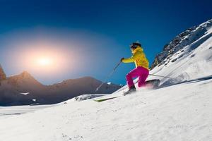 meisje maakt skiën in telemark-techniek op zonnige dag op de berg foto