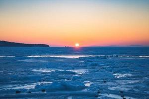 zeegezicht met zonsondergang over het ijzige oppervlak in Vladivostok, Rusland foto