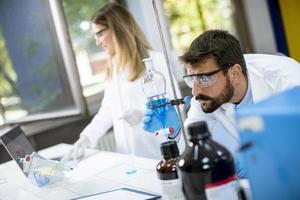 onderzoekers die met blauwe vloeistof aan de scheitrechter werken foto