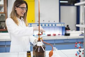 vrouwelijke onderzoeker in beschermende werkkleding permanent in het laboratorium en kolf met vloeibaar monster analyseren foto