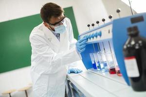 jonge onderzoeker met veiligheidsbril reageerbuisjes in flocculator controleren foto